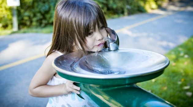 Photo Girl drinks from drinking fountain
